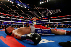 Roman Martinez lays prone on the canvas as Vasyl Lomachenko raises his arms in victory. Photo / Getty