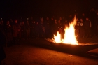 A flame lit during Puanga karakia at Mt Ruapehu arrives on the Whanganui River. Photo/ Laurel Stowell