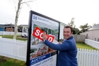 Agent Mike Proctor slapping the sold sign on the house that set a new high. Photo / John Stone