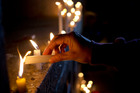 A man in Santiago, Chile, lights a candle during a vigil in front of the US Embassy to remember the victims of the mass shooting at the Pulse Orlando. Photo / AP
