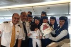 Pilots and flight staff pose with the newborn baby born on the Saudi Arabian Airlines flight. Photo / Twitter, @SultanALFuraih1