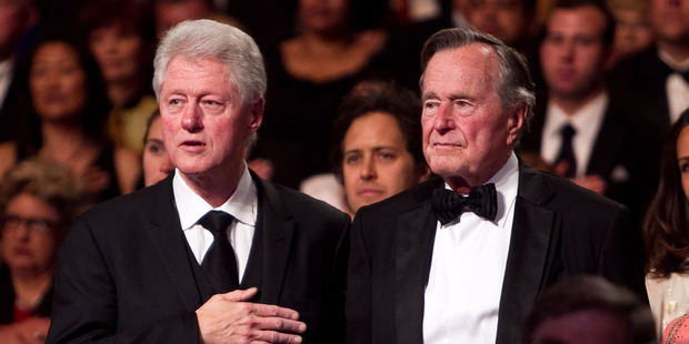 Former President Bill Clinton (L) and former President George H.W. Bush stand for the National Anthem. Photo / Getty