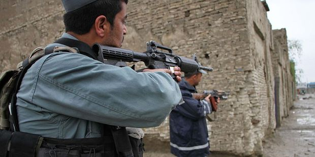 Afghan policemen keep guard at the site of the Taliban attack in front of Afghan intelligence office. Photo / Getty Images