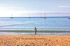 Rob Cox takes an early-morning walk on Oneroa beach.