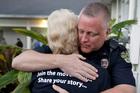 Orlando Police Lt. James Young hugs Karen Castelloes after a prayer vigil. Photo / Associated Press