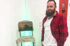Brett Morrison with the chair that he made, which sold for $550.