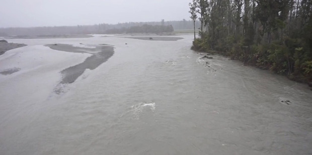 The 4WD submerged in the flooded Poerua River in flood, near Harihari on the West Coast. Emily Saunders, 2, and Barry Petrie, 66, lost their lives. Photo / West Coast Air Rescue Trust