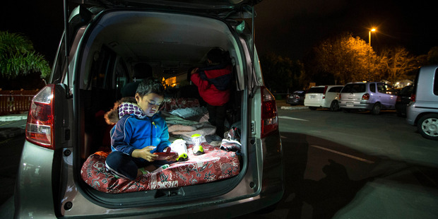 Setima Autagavaia, 4, in the back of his family vehicle for Park Up for Homes in Mangere Town Centre car park. Photo / Jason Oxenham