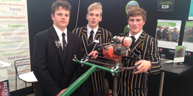 Angus Kelly (black jacket), Hugh Jackson (centre) and Connor Gordon with their award-winning invention the crankholder. Photo / Supplied