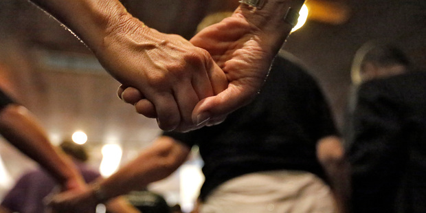 Loading People at a pray vigil at the Joy Metropolitan Church hold hands after the fatal shooting. Photo / AP