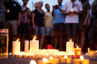 Mourners gather around candles lit during a vigil after a fatal shooting at the Pulse Orlando nightclub. Photo / AP