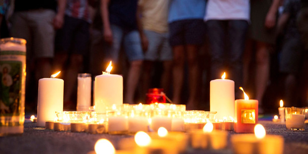 Loading Mourners gather around candles lit during a vigil after a fatal shooting at the Pulse Orlando nightclub. Photo / AP
