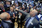 Specialist Philip Finale, right, directs trading on the floor of the New York Stock Exchange. Photo / AP