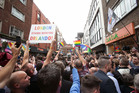 People gather on Old Compton Street, London, during a vigil for the victims of Sunday's Orlando shootings at a Gay nightclub in Florida. Photo / AP