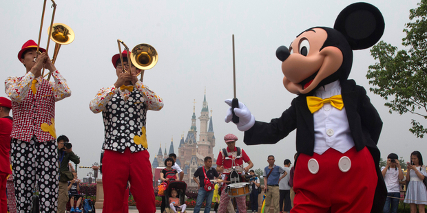 Mickey Mouse entertains visitors on the opening day of Shanghai Disneyland. Photo / AP
