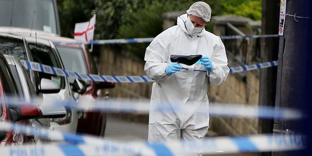 A forensics officer looks at a woman's shoe at the scene where Labour MP Jo Cox was killed. Photo / AP