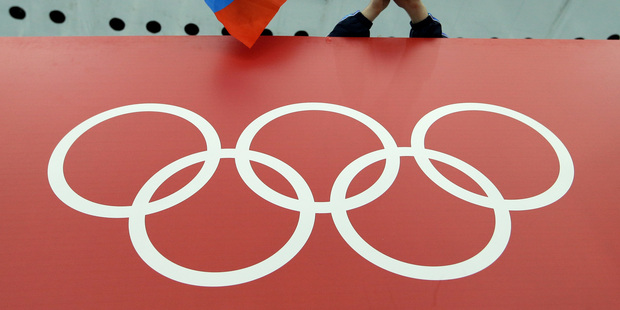 FILE - In this Feb. 18, 2014, file photo, a Russian skating fan holds the country's national flag over the Olympic rings before the start of the men's 10,000-meter speedskating race. Photo / AP.