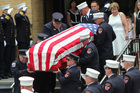 Theresa Stack follows her husband's flag-draped casket. Photo / AP