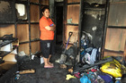 Cathlyn Pala stands in the burnt out wreckage of her home in Mangere. She rescued her three nieces when fire broke out in the morning of 12 May 2016. Photo / Susan Strongman