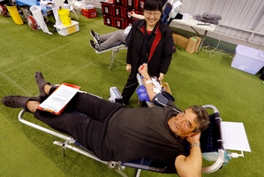 Winnie Wang looks on as Charles Frische gets to lay down doing something very special - donating his blood for the 58th time. Photo / John Stone