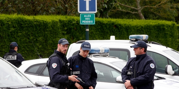 French police officers block the road leading to the crime scene. Photo / AP