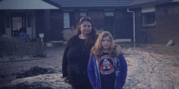 MUD BATH: Kylie Bishop and her daughter Jessica in what remained of their front garden, June 2015.