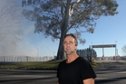 Resident/landowner Tyson  makes his point along Sandy Rd, Meeanee, in Napier, as smoke drifts onto his property  in the background last Saturday during a speedway burnout meeting. Photo / Duncan Brown