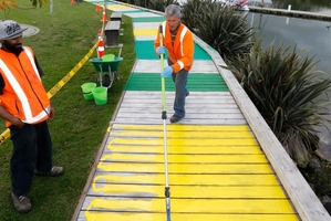 Contractors John Grounden (left) and Michael Coote apply a colourful non-skid coating to Hatea Loop Walkway. Photo / John Stone