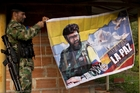 A Farc fighter in the group's hidden camp in Antioquia state hangs a banner featuring the late rebel leader Alfonso Cano. Photo / AP