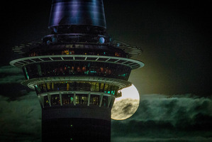 Visitors up Auckland's Skytower get a good view of the full moon rising over east Auckland on the eve of Winter Solstice. Photo / Jason Oxenham