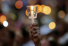 A supporter of the victims of the recent mass shooting at the Pulse nightclub holds up a candle at a vigil at Lake Eola Park, Orlando. Photo / AP