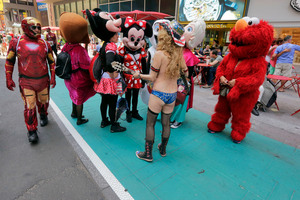 Costumed characters, including The Naked Cowgirl, gather in one of New York's Times Square new colour-coded designated activity zones. Photo / AP