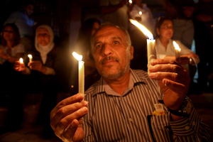 Jordanians hold candles at a vigil for six Jordanian soldiers killed in a suicide bombing on their border with Syria, in Amman Jordan. Photo / AP