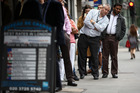 A customer looks along a line outside a foreign currency exchange bureau in London. Photo / Bloomberg