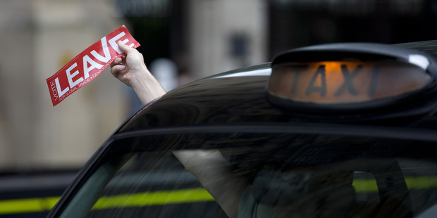 """A Black Cab driver holds a """"vote leave"""" sticker out his window. Photo / Getty"""