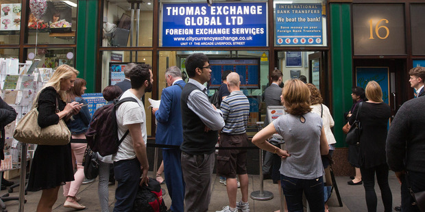 Loading Customers queue outside a foreign currency exchange bureau in London. Photo / Bloomberg