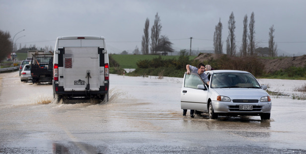 Loading Hamish Jellyman gets a hand from a fellow motorist to push his broken-down car out of flood waters that covered State Highway 2 near Pukehina Beach in the Bay of Plenty. Photo / Alan Gibson