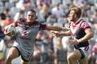 Warrior Tui Lolohea shows off his speed as he fends off a Roosters attack. Photo / Getty Images