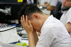 A currency trader rubs his eyes at the foreign exchange dealing room in Seoul, South Korea. Photo / AP