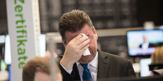 Robert Halver of Baader Bank wipes his face in the trading hall of the Frankfurt, Germany, stock exchange Friday morning. Photo / AP
