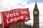 Leave supporters hold flags as they stand on Westminster Bridge. Photo / AP