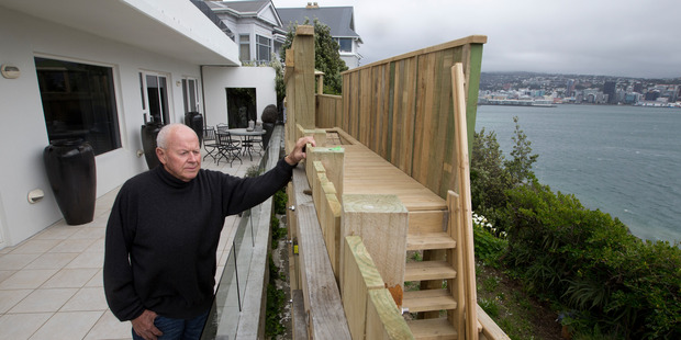 Peter Aitchison and the four-metre-high wooden fence that blocked the view of Wellington City and Harbour from his apartment in Roseneath. Photo / Mark Mitchell