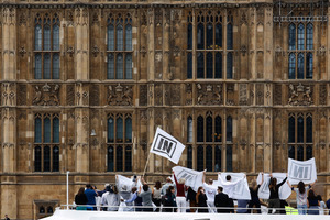 Campaigners for the Remain campaign demonstrate in on the deck of a boat as it passes outside the Houses of Parliament in London. Photo / Bloomberg