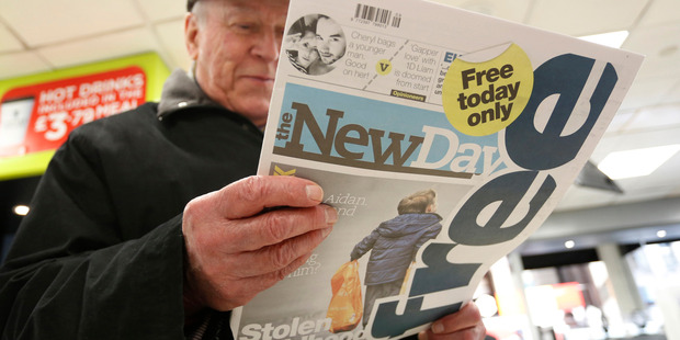 A pedestrian reads the newly launched The New Day newspaper - the paper closed in less than three months. Photo / Luke MacGregor