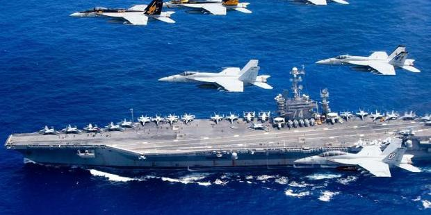A combined formation of aircraft from Carrier Air Wing (CVW) 5 and Carrier Air Wing (CVW) 9 pass in formation above the Nimitz-class aircraft carrier USS John C. Stennis. Photo / Getty Images