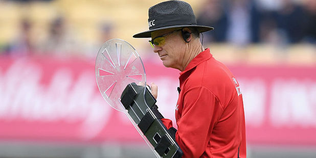 Umpire Bruce Oxenford holds his custom-built protective shield. Photo / Getty Images