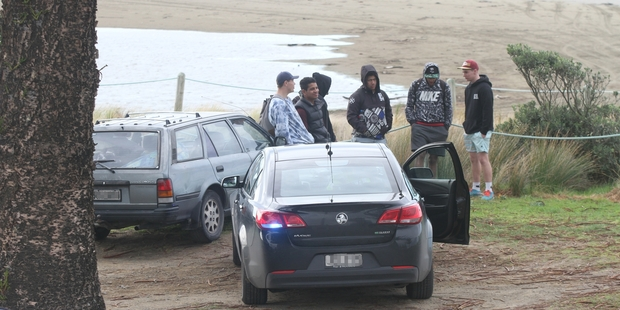 Six youngsters wait beside their car outside the Riversdale Surf Life Saving Club while an officer in an unmarked police car checks their details.
