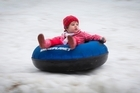 Three year old Emma Martin (Contact mum Leeann 021745910) enjoys a ride on the snow hill at Royal Reserve, Massey as part of Snow in the Park on Sunday. 26 June 2016 New Zealand Herald Photograph by Greg Bowker