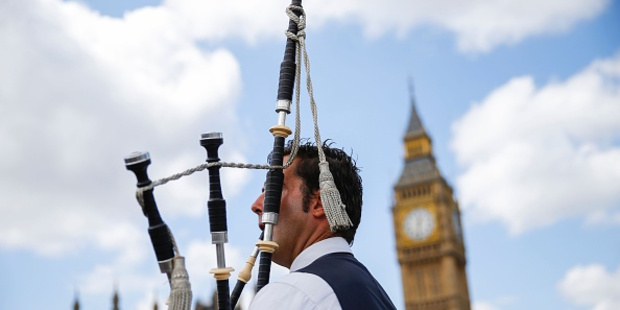 Loading A Scottish piper plays for tourists in front of the Houses of Parliament in central London. Photo / Getty Images