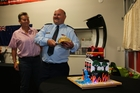 Paihia fire chief Shane Schrafft, cutting into his farewell cake at a function at the station last Saturday night.  More than 105 community dignitaries, senior police, fire and ambulance officers, and family were present. Photo / Fits Schouten